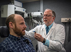 Dr. M. Patrick Feeney is director of the National Center for Rehabilitative Auditory Research. He is pictured with a VA employee, demonstrating a hearing test. <em>(Photo by David M. Moody, VA Portland Health Care System, Oregon)</em>