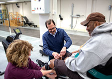 Dr. Ronald J. Triolo and physical therapist Lisa Lombardo work with a Veteran research participant in the VA Motion Study Laboratory in Cleveland. (Photo by Jennifer Kerbo)
