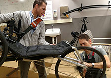 VA investigators Drs. John McDaniel and Paul Marasco adjust a tricycle designed to be used by a person with complete spinal cord injury and an implanted neural stimulation device. (Photo by Nathaniel Welch)