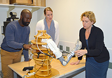 (From left) Research health science specialist Frantzy Acluche and project coordinator Sarah Ekerholm discuss the DEKA arm, an advanced upper-limb prosthesis, with Dr. Linda Resnik. (Photo by Kimberly DiDonato)