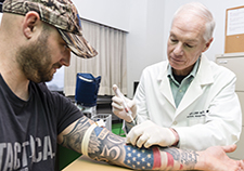 Dr. William Walker is seen with Joe Montanari, who served in the Army from 1999 –2008, including duty in Iraq.  Montanari works as a research assistant at the Richmond VA Medical Center. The TBI study led by Walker will include blood tests to check for certain genetic factors, in addition to brain scans, exams, and many other measures. (Photo by Jason Miller)