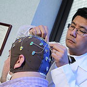 Dr. K. Luan Phan adjusts a volunteer's electrode cap. The researcher is studying the brain's