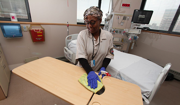 Karen Curtis, with Environmental Services at the Baltimore VA Medical Center, cleans a patient room in the hospital's intensive care unit. (Photo by Mitch Mirkin)