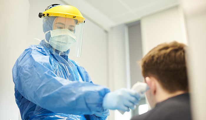 Photo of health care worker in full protective gear taking a patients temperature