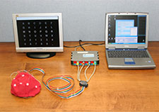 The photo shows the elements of the Wadsworth brain-computer interface. The user wears the electrode-fitted cap. (Photo courtesy of Wadsworth Center)