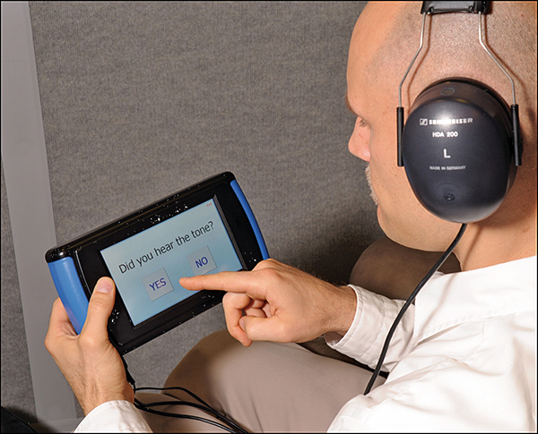 A study participant uses the OtoID system to test his hearing