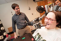 Jan Scheuermann, who has quadriplegia, prepares to take a bite out of a chocolate bar she has guided into her mouth with a thought-controlled robot arm. Research assistants Drs. Brian Wodlinger and Elke Brown watch in the background. (Photo: UPMC))