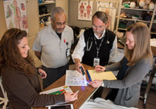 Clockwise: Infection preventionist Nicole Gerdts and Environmental Services staffer Bobby Cole discuss cleaning practices with researchers Dr. Eli Perencevich and Dr. Heather Reisinger at the Iowa City VA Health Care System. (Photo by Steve Smith)