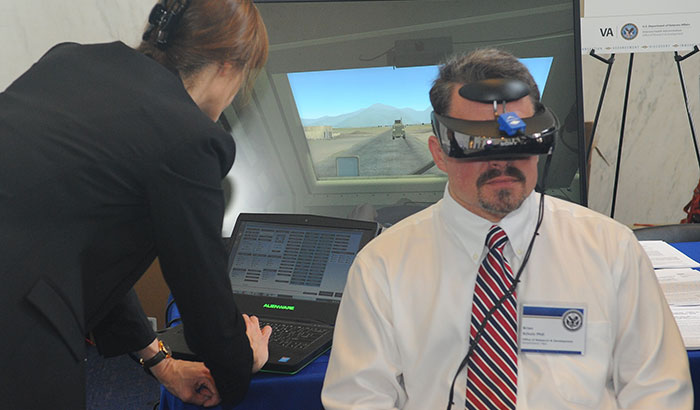 In the photo, taken at a VA research exhibit on Capitol Hill in June 2019, a VA staffer tries on a virtual reality headset. (Photo by Robert Williams)