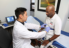 Research technician Michael Tam fits a finger probe on Ralph Liggins, part of a system that will monitor his sleep at his home. (Photo by Jerry Daliege)