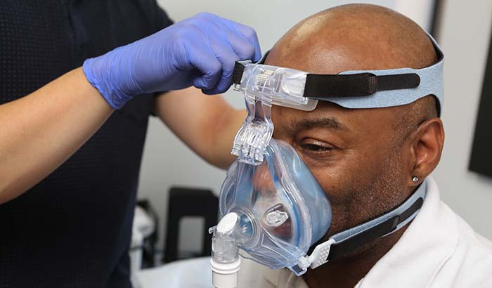 Ralph Liggins tries on a CPAP mask at the Jesse Brown VA Medical Center in Chicago. <em>(Photo by Jerry Daliege) </em>