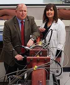 Drs. David Cook and Elaine Peskind use a device called a shock tube (shown in foreground) to simulate blasts in rodent models so they can better understand what happens in the brains of soldiers exposed to blasts. (Photo by Christopher Pacheco)