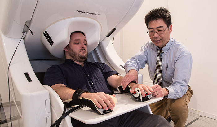 """Pictured: Dr. Mingxiong Huang prepares to do a MEG brain scan on a """"healthy control"""" who has participated in his neuroimaging research. (Photo by Kevin Walsh)"""