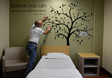 Tony Wickliffe, with the Media Resources group at the Central Arkansas Veterans Healthcare System, applies a mural in a room on an inpatient psychiatric unit. In accord with VA's Mental Health Environment of Care Checklist, the Little Rock facility uses such artwork to avoid conventional picture frames, which could potentially be a hazard.