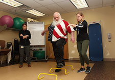 Army Veteran Gary Lucas navigates a hurdle exercise with the help of study coordinator Lydia Paden. (Photo by Mitch Mirkin) )