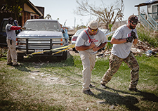 Many Team Rubicon volunteers took part in rescue efforts in the aftermath of Hurricane Harvey, which ravaged parts of southeastern Texas in August 2017. Here, former Army Green Beret Brighton Timmins (L) and firefighter Samson Rivera pull a disabled truck out of the way of a home in Rockport, Texas. (<em>Photo by</em> <em>Matt Mateiescu</em>