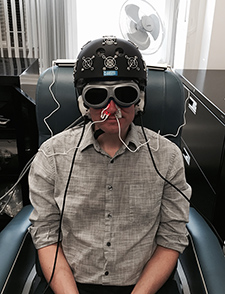 A staffer in Dr. Margaret Naeser's lab demonstrates the equipment built especially for the research: an LED helmet (Photomedex), intranasal diodes (Vielight), and LED cluster heads placed on the ears