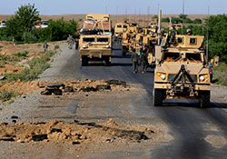 On a southern Afghanistan road in 2010, U.S. Army troops pass by craters that had been created just hours before by improvised explosive devices. IEDs havebeen the main cause of traumatic brain injuries among U.S. troops in recent wars.