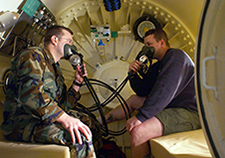 Two Navy divers test breathing masks inside a recompression chamber. The chamber is used to treat diving-related disorders and other medical conditions with hyperbaric oxygen therapy.