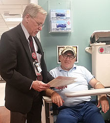 Dr. John Callaghan chats with Army Veteran Robert Knight, who served 25 years in the 82<sup>nd</sup> Airborne Division, as Knight prepares to provide a blood sample as part of his enrollment in VA's Million Veteran Program.