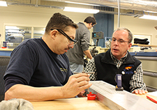 Cooper (right) explains to retired Marine Gunnery Sgt. James Joseph part of a device that is being made in HERL's Advanced Inclusive Manufacturing Training program. The device is the PathLoc Mobile caster.