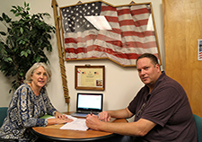 Social worker Karen Ablondi, a research associate with Dr. Jack Tsai's team, meets with Veteran Thomas Scherrer as part of a pilot program to teach money management to clients of the HUD-VASH program. <em>(Photo courtesy of Jack Tsai)</em>