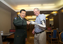 Fred Downs Jr., former chief of prosthetics and sensory aids for VA, wears the DEKA prosthetic arm as he shares a
