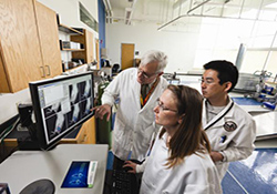 Dr. Jeffery Kocsis (left), Heather Mallozzi, and Dr. Masanori Sasaki, with the West Haven VA and Yale University, view in vivo images of neural repair that