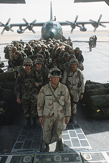 Army troops wait to board a C-130 for the trip to Fort Bragg, N.C., following the liberation of Kuwait during Operation Desert Storm. Behind the troops is another C-130 Hercules aircraft.s