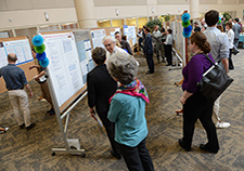 Staff and visitors check out scientific posters during a National VA Research Week event last year at the Minneapolis VA Health Care System. <em>(Photo by April Eilers)</em>