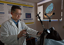 Dr. Albert Leung is testing whether transcranial magnetic stimulation can ease headaches associated with head trauma. <em>(Photo by Kevin Walsh)</em>