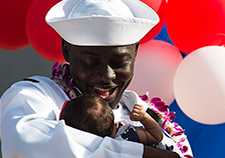 Navy Petty Officer 2nd Class Komla Amewouame meets his daughter for the first time after returning to Pearl Harbor, Hawaii, in December 2015 after a seven-month deployment on the USS Chafee. (Photo by Petty Officer 2nd Class Laurie Dexter/USN